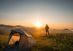 A man standing outside at sunset next to a tent